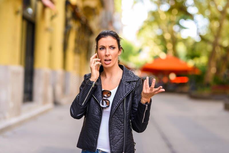 En ung kvinna som förargas, medan genom att använda hennes telefon i en stads- envir arkivbilder