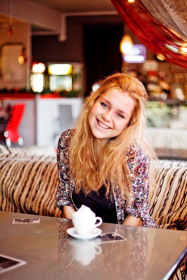 En ung kvinna som har lunch på skratta för cafe arkivbild