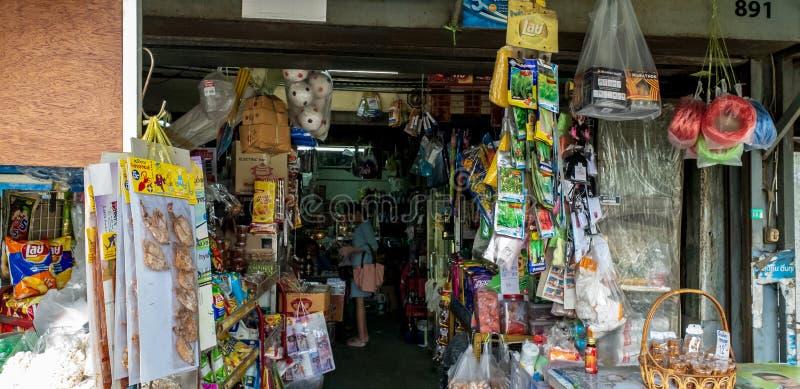 En ung kvinna som köper någon förbrukningsartikel i gammal gata för specerihandlare` s, shoppar arkivbilder