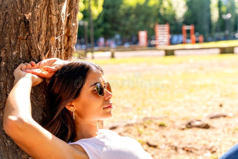 En ung kvinna som ligger bredvid ett träd och njuter av solsken arkivfoton