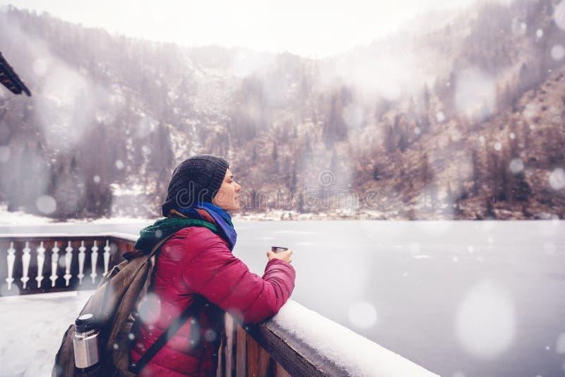 En ung kvinna som reser i bergen i vintern som dricker varmt te mot bakgrunden av en djupfryst sjö, fjällängarna royaltyfria bilder