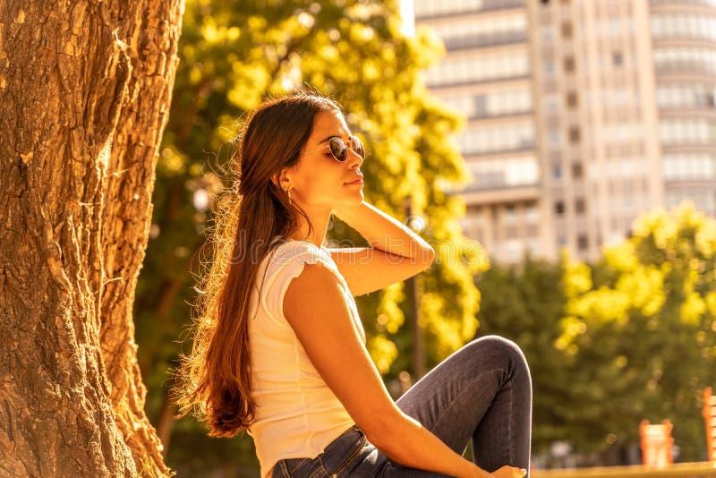 En ung kvinna som sitter bredvid ett träd och njuter av solsken royaltyfria bilder