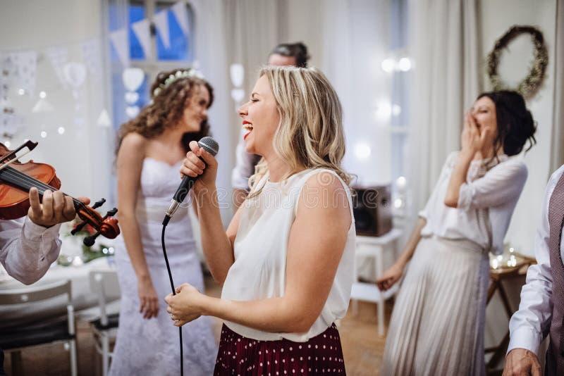 En ung kvinna som sjunger på ett gifta sig mottagande, en brud och en gästdans arkivbilder