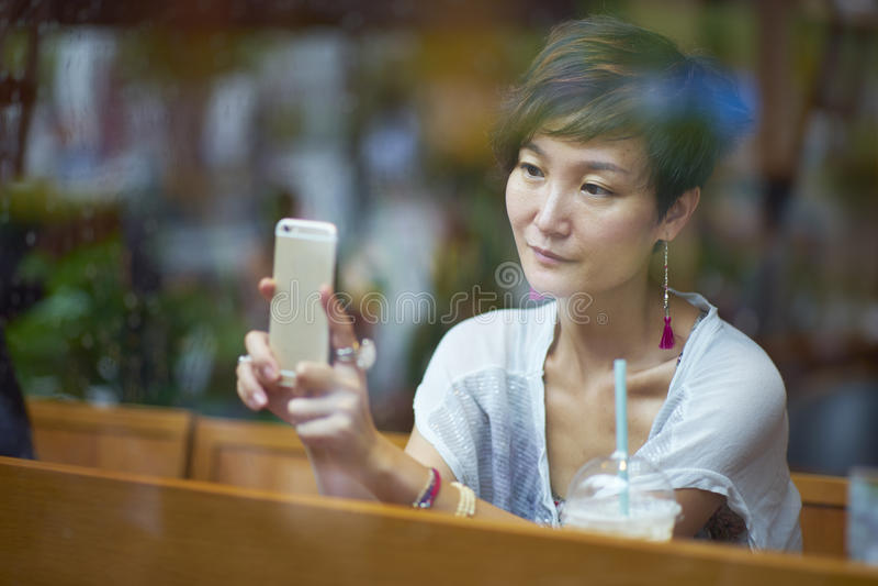 En ung kvinna som tar fotoet med hennes smartphone arkivbild
