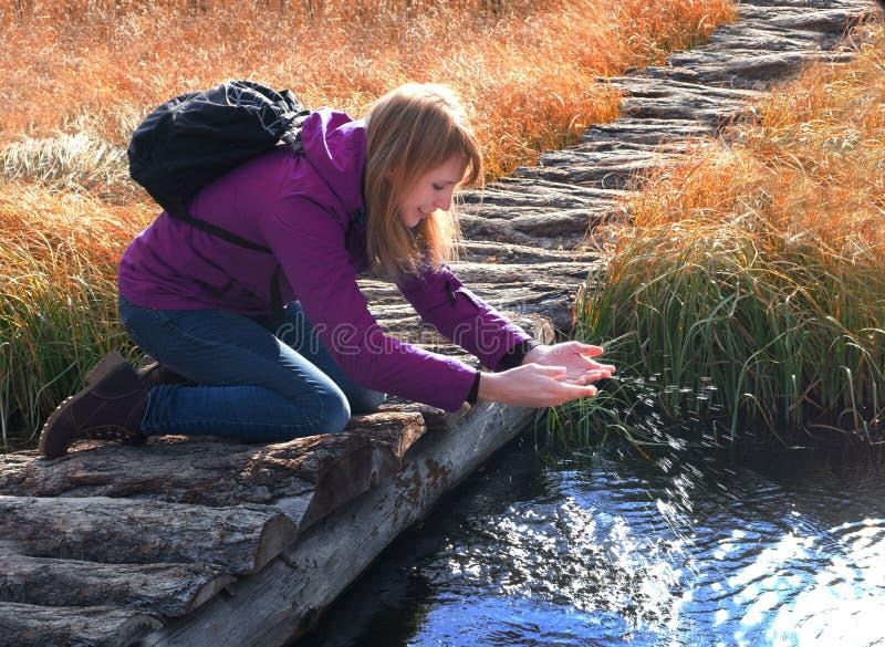 En ung kvinna spelar med vatten i en liten vik Solstrålar på sprejen av vatten royaltyfri foto