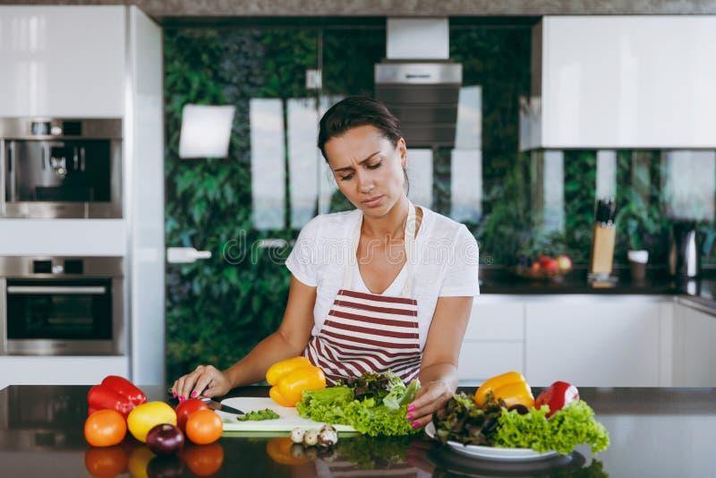 En ung kvinna spenderar tid hemma, i köket och i rooen royaltyfria foton