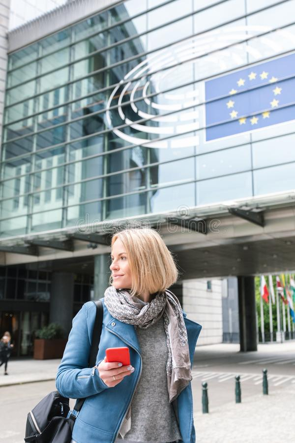 En ung kvinna står med en telefon i hennes händer mitt emot Europaparlamentetbyggnaden i Bryssel, Belgien arkivbild