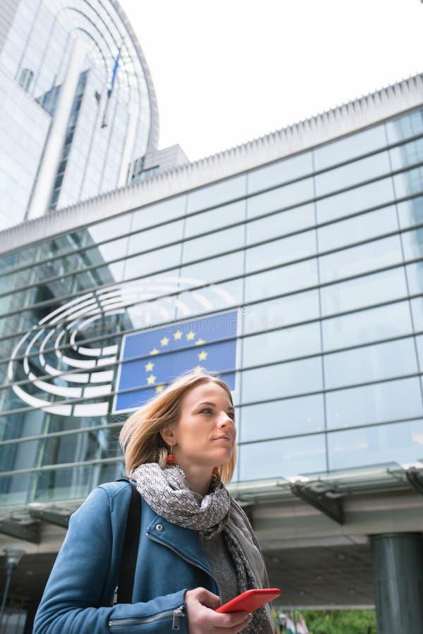 En ung kvinna står med en telefon i hennes händer mitt emot Europaparlamentetbyggnaden i Bryssel, Belgien royaltyfri bild