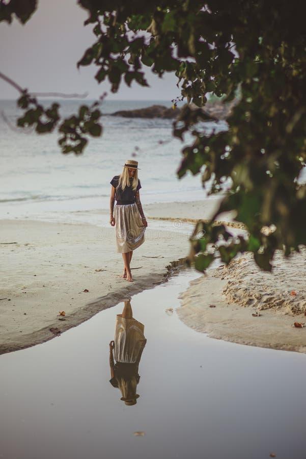 En ung kvinna står på det lugna vattnet i ottan Sandig strand med frodiga gröna träd En semester i Thailand arkivbild