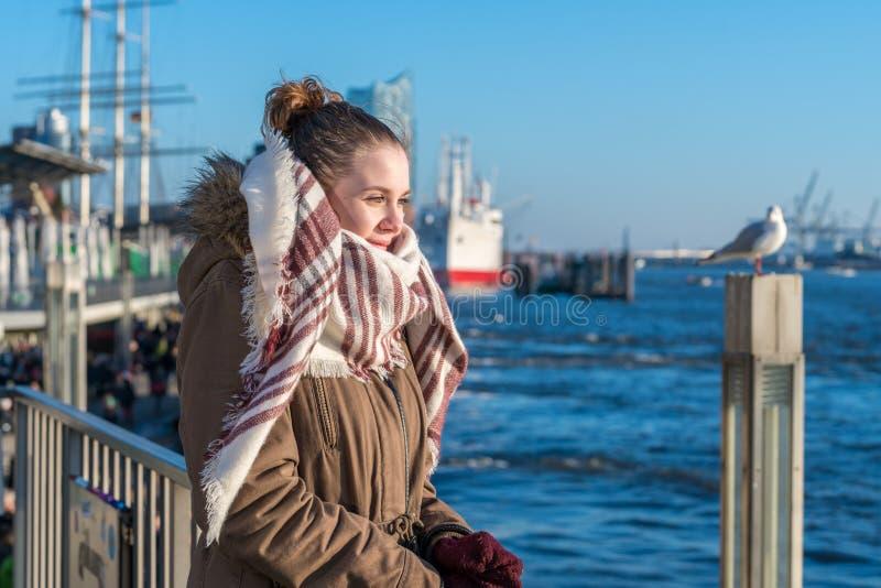En ung kvinna står på en pir som ser vattnet royaltyfri bild