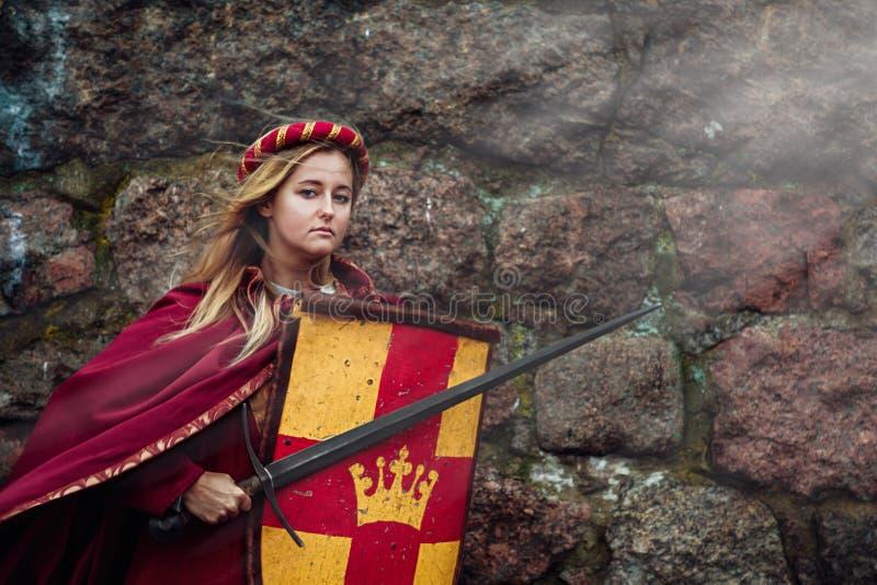 En ung kvinna står på skyddet av kungariket med ett svärd och en sköld i hennes händer arkivfoto