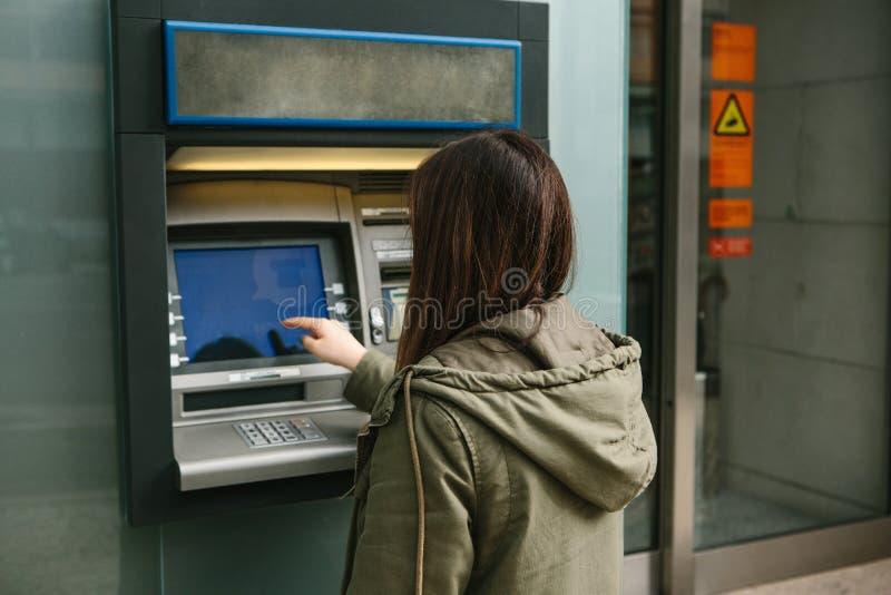 En ung kvinna tar pengar från en ATM Griper ett kort från ATMEN Finans kreditkort, tillbakadragande av pengar fotografering för bildbyråer