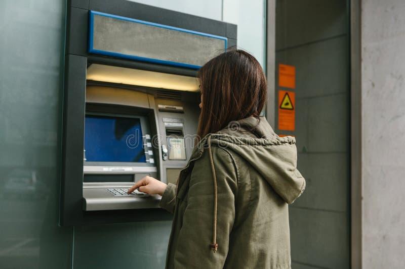 En ung kvinna tar pengar från en ATM Griper ett kort från ATMEN Finans kreditkort, tillbakadragande av pengar arkivfoto