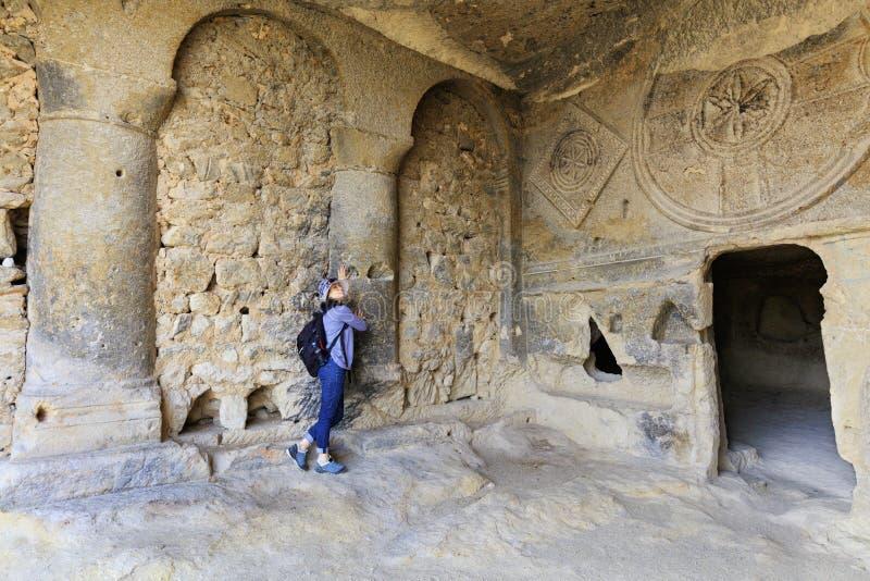 En ung kvinna undersöker inre av den gamla underjordiska church'skolonnkorridoren som snidas in i en sandstenklippa arkivfoto