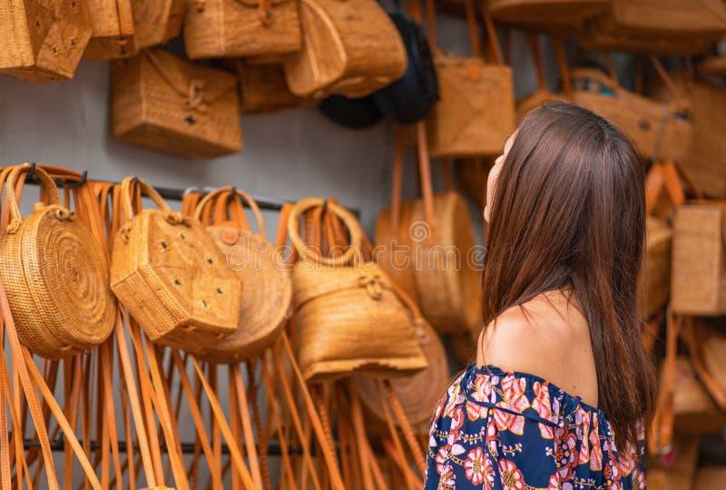 En ung kvinna väljer en vide- påse i lagret Asiatiska flätade påsar close upp arkivfoton