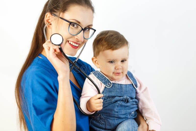 En ung kvinnlig doktor rymmer behandla som ett barn i hennes armar, och behandla som ett barn ler på en stetoskop Vit bakgrund royaltyfri bild
