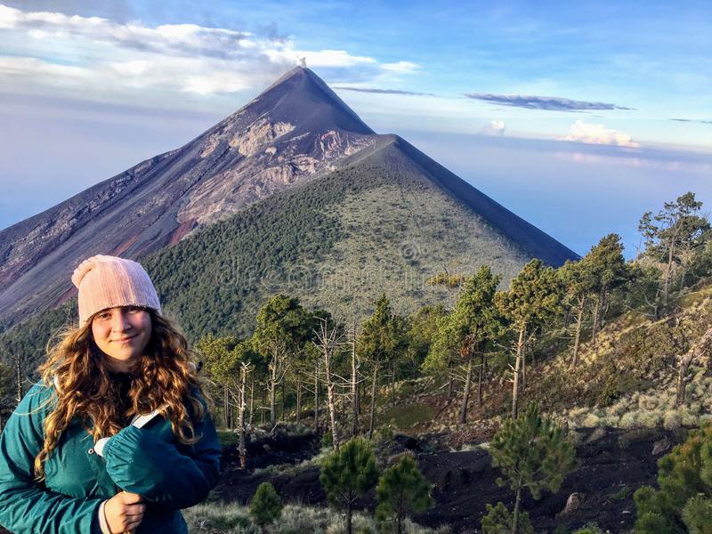 En ung kvinnlig turist som ler bredvid hennes tältplats på vulkanmonteringen Acatenango royaltyfria bilder