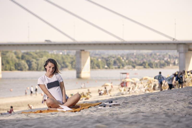 En ung le flicka och att posera och att se kameran som sitter i filt på den sandiga stranden royaltyfri bild