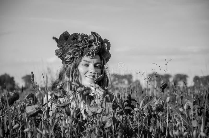 En ung, lycklig härlig flicka har gyckel, och att dansa med glädje i fältet av blomningvallmo med en krans av vallmo blommar arkivfoton