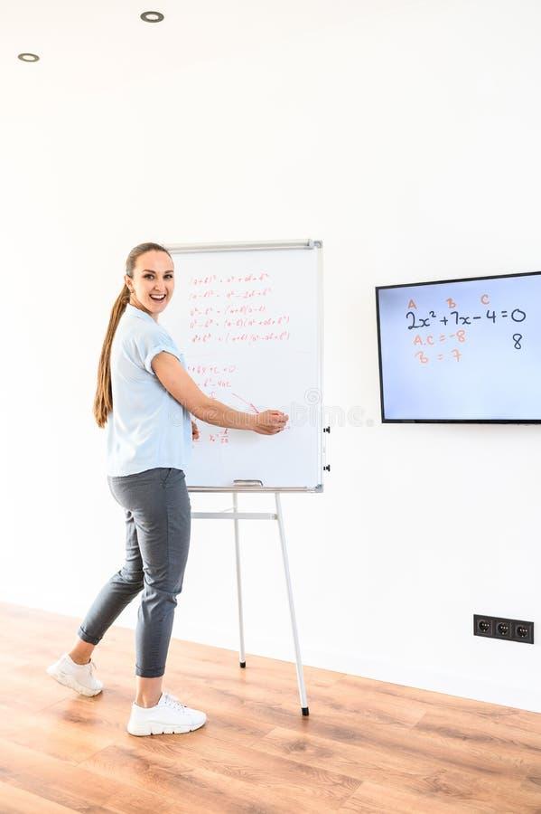 En ung lycklig kvinna använder flip-diagram och bildskärm för att undervisa arkivfoton