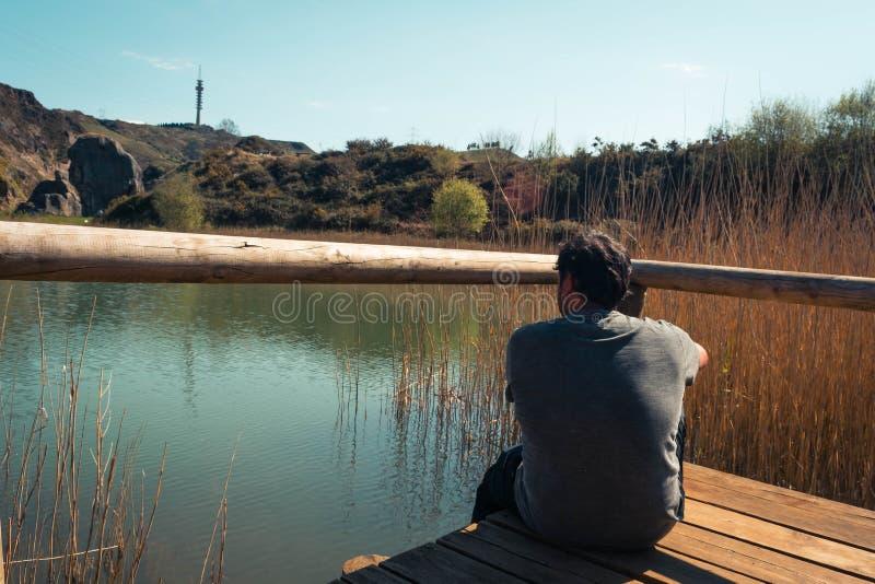 En ung man bara p? en sj?, st?ende, laarboleda, basque land arkivfoto