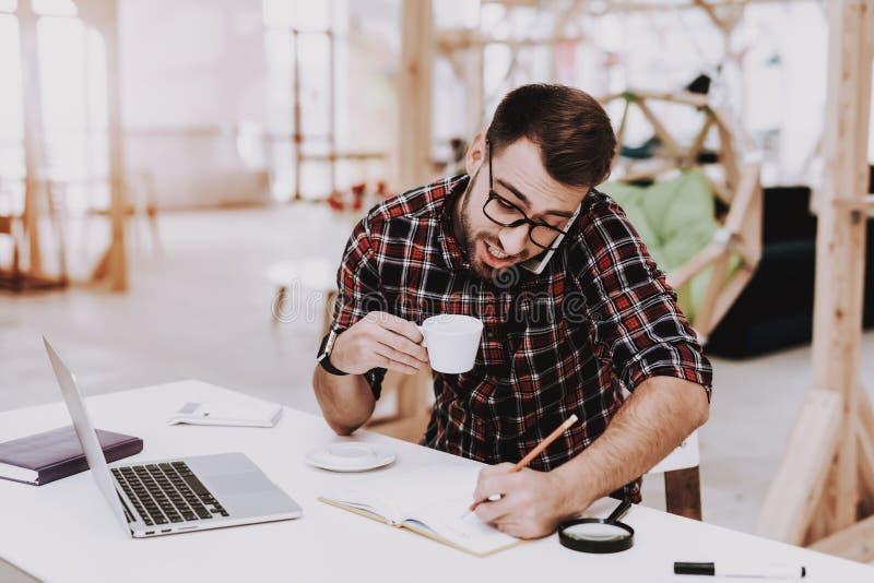 En ung man dricker kaffe på arbete royaltyfri fotografi