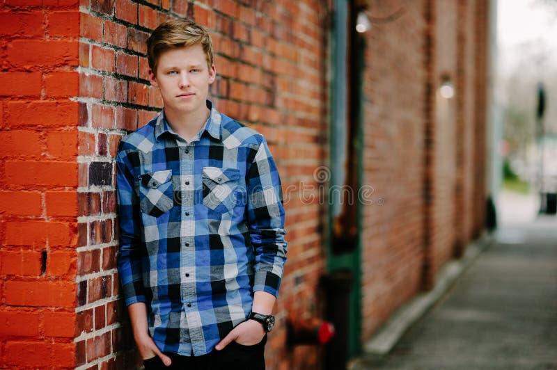 En ung man för handsom lutar mot en tegelstenvägg i en gränd. royaltyfria bilder