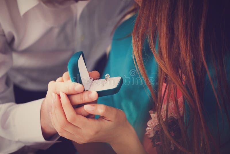 En ung man gör ett förbindelseförslag till hans flickvän och förvånar henne med en härlig förlovningsring royaltyfria bilder