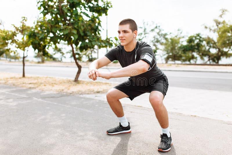 En ung man gör en morgon att jogga i gatorna, sportutbildning royaltyfri fotografi