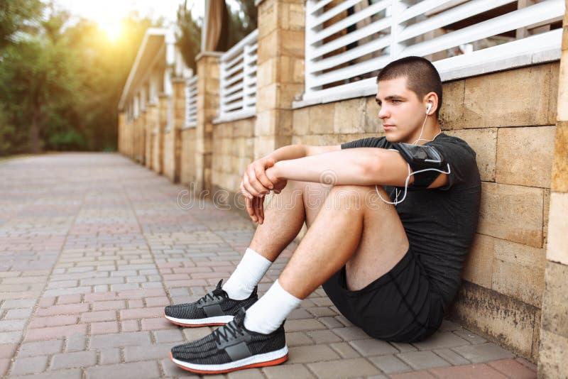 En ung man gör en morgon att jogga i gatorna, sportutbildning royaltyfri bild