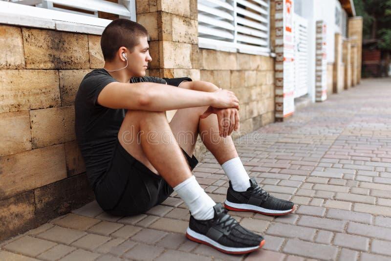 En ung man gör en morgon att jogga i gatorna, sportutbildning arkivfoto