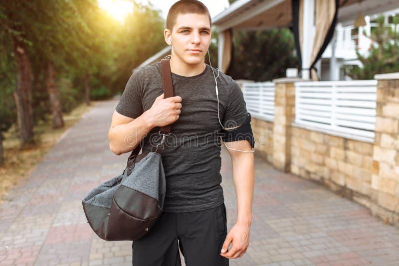 En ung man gör en morgon att jogga i gatorna, sportutbildning arkivbild