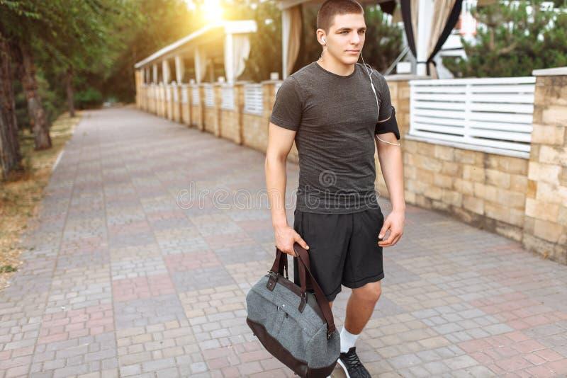 En ung man gör en morgon att jogga i gatorna, sportutbildning royaltyfri foto