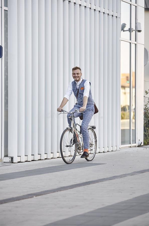 En ung man, 20-29 gamla år, bärande hipsterdräkt, smart tillfälligt, ridning som cyklar på den gamla stadscykeln vit modern väggb arkivfoto