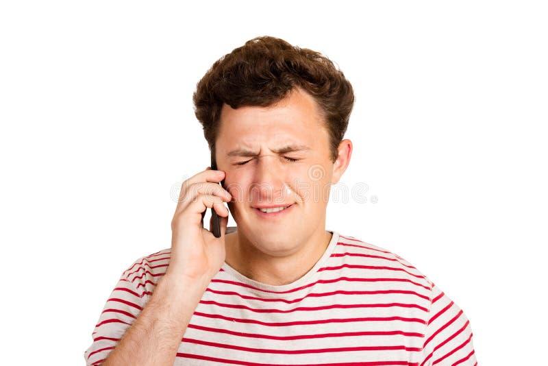 En ung man gråter om dåliga nyheter genom att stänga hans ögon och att tänka om problemet att han får på hans telefon emotionell  arkivfoto