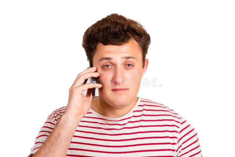 En ung man gråter om dåliga nyheter genom att stänga hans ögon och att tänka om problemet att han får på hans telefon emotionell  royaltyfri foto