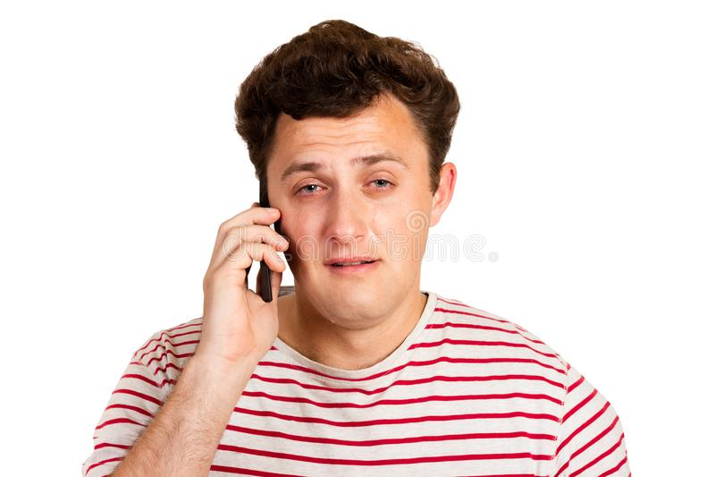 En ung man hörde dåliga nyheter på telefonen och börjar att gråta emotionell man som isoleras på vit bakgrund royaltyfri foto