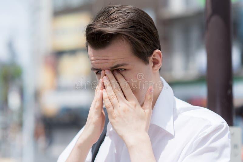 En ung man har kliande, vattnig svullen pollenallergi för ögon tack vare arkivfoton