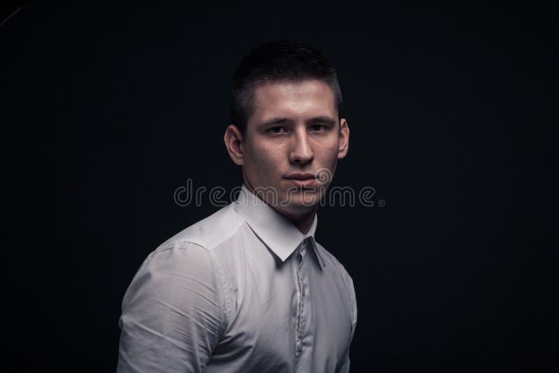 En ung man, head framsidaheadshot åt sidan, svart bakgrund royaltyfria foton