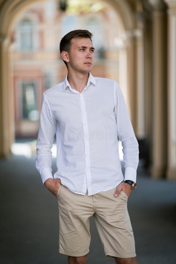 En ung man i beigea bakstycken för en vitskjorta rymmer hans händer i fack på en färgrik suddig bakgrund royaltyfria bilder