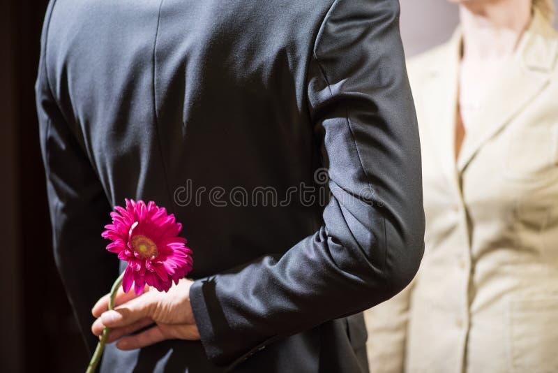 En ung man i en dräkt rymmer en gerberablomma bak hans baksida, en överraskning för en kvinna, mars 8 arkivfoton