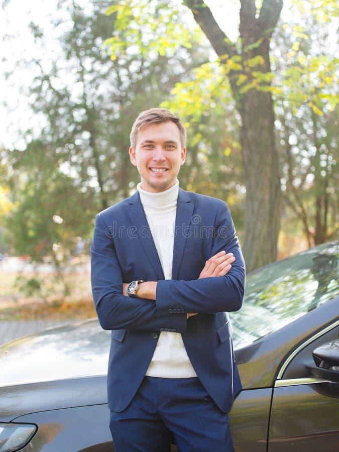 En ung man i en dräkt står nära bilen med hans vikta armar och att le utanför arkivfoton