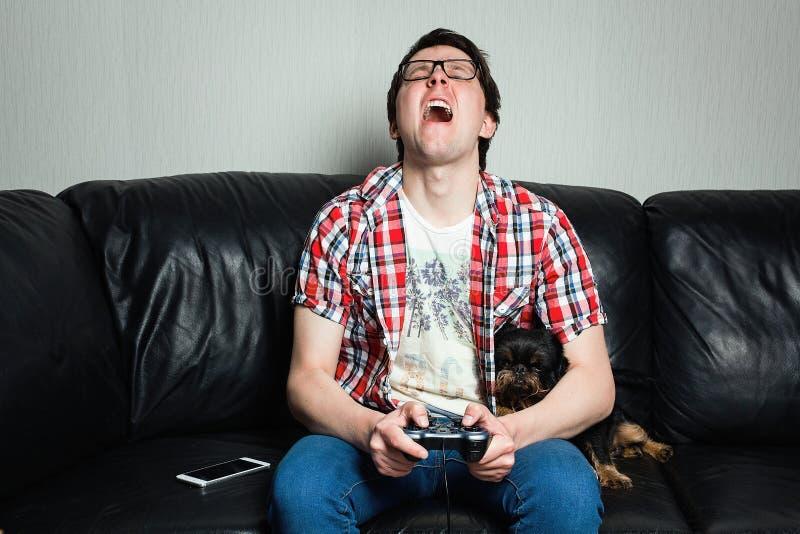 En ung man i en röd skjorta och jeans sitter hemma och spelar videospel samman med deras hund Den fattiga grabben är skriande och fotografering för bildbyråer