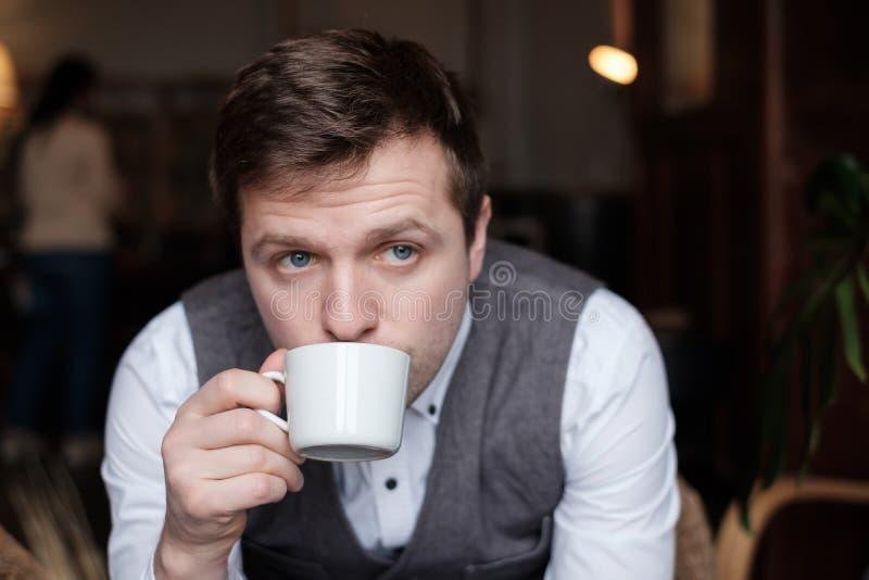 En ung man i en vit skjorta och waistcoat frukosterar arkivbilder