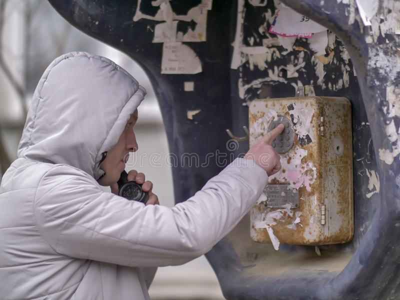 En ung man i ett grått omslag med en huv kallar från en gammal payphone på gatan royaltyfri foto