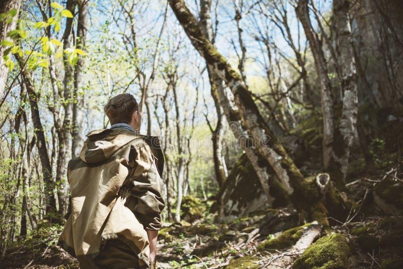 En ung man i lägerkläder och med en svans på hans head blickar och beundrar storheten av naturen, vaggar och berget royaltyfri fotografi