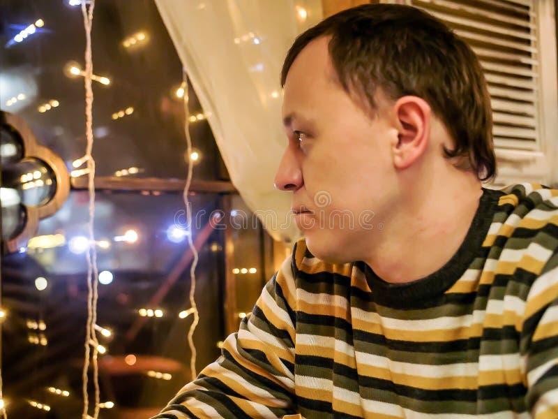 En ung man i en randig tröja sitter i aftonen i ett kafé ser ut fönstret royaltyfria foton