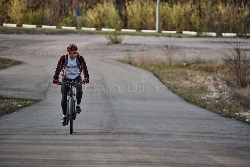 En ung man i sportkläder rider en cykel fotografering för bildbyråer