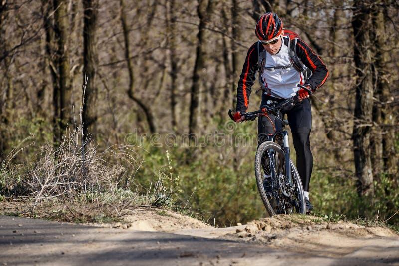 En ung man i sportkläder rider en cykel royaltyfri bild