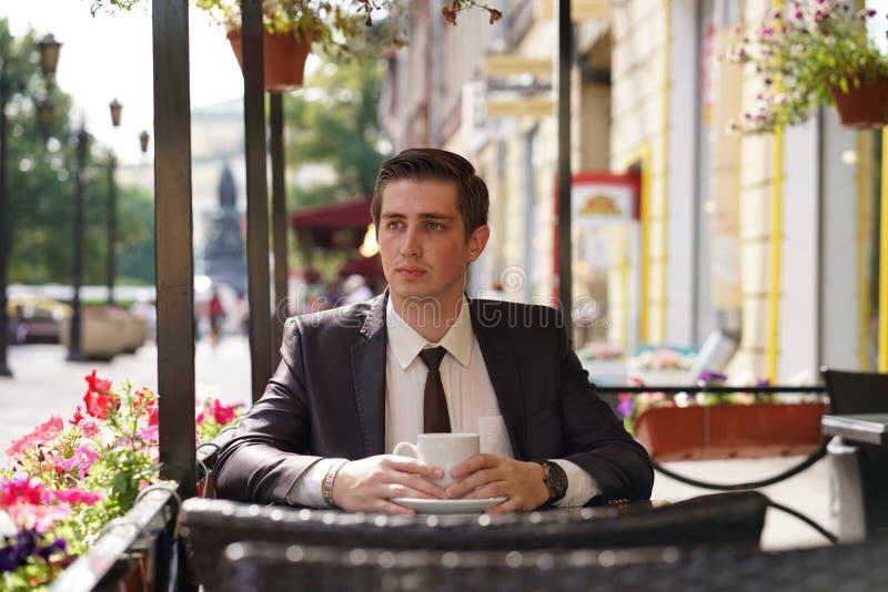 En ung man i en svart affärsdräkt, en vit skjorta och ett band sitter i ett stadsgatakafé på en tabell och tycker om en kopp kaff royaltyfri bild